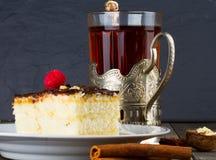 Испеките с сливк шоколада и чашкой чаю в держателе чашки  Стоковое Фото