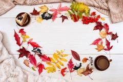 Испеките, черный chokeberry, красная рябина, листья осени и чашка кофе с молоком на светлой предпосылке Блюда глины Бежевый Джерс стоковое изображение