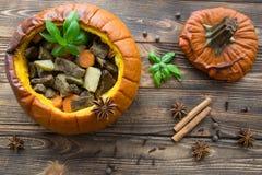 Испеченная еда в тыкве на деревенской коричневой деревянной предпосылке потушено стоковое фото rf