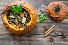 Испеченная еда в тыкве на деревенской коричневой деревянной предпосылке потушено стоковые изображения