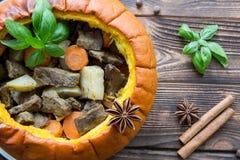 Испеченная еда в тыкве на деревенской коричневой деревянной предпосылке потушено стоковое изображение