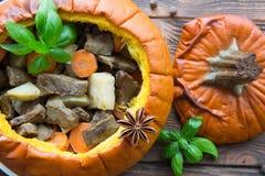 Испеченная еда в тыкве на деревенской коричневой деревянной предпосылке потушено стоковое фото