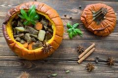 Испеченная еда в тыкве на деревенской коричневой деревянной предпосылке потушено стоковые фото