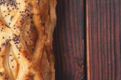 Испеченная плюшка при печенье слойки, взбрызнутое с маковыми семененами на темной деревянной предпосылке Конец-вверх еда варенико Стоковые Изображения