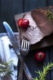 Испеченное мясо с розмариновым маслом и красным перцем Стейк bedroll обедающий для людей Темное фото Черная предпосылка Деревянна стоковая фотография