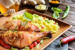 Испеченные бедренные кости цыпленка с медом, заскрежетанным имбирем и рисом с турмерином Стоковое фото RF