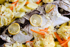 Испеченные белые рыбы с кусками лимона, морковами и Стоковое фото RF