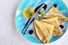 Испеченные блинчики с медом мяты напудрили сахар и соус на голубой плите стоковая фотография