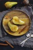Испеченные груши в сиропе карамельки послужены на деревянной плите на темной предпосылке Стоковые Изображения