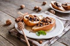 Испеченные груши с медом, грецкими орехами, клюквами миндалины и циннамоном Стоковая Фотография RF