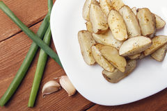 Испеченные картошки с зелеными луками на белой плите Стоковая Фотография RF