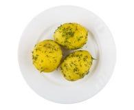 Испеченные картошки с укропом на плите изолированной на белой предпосылке Стоковое Изображение