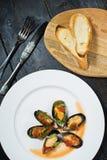 Испеченные мидии в томатном соусе с кориандром и пармезаном на белой плите стоковое фото