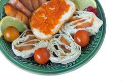 Испеченные рыбы и овощи на плите на белой предпосылке Стоковое Изображение