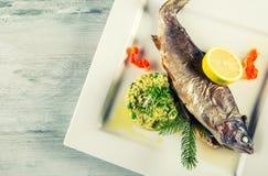 Испеченные рыбы на плите с гроутами лимона и ячменя в ресторане Стоковое Изображение