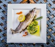 Испеченные рыбы на плите с гроутами лимона и ячменя в ресторане Стоковые Изображения RF