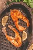 Испеченные рыбы форели стейка в чугуне формируют, вокруг зеленых цветов, листья, Стоковые Изображения