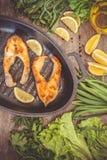 Испеченные рыбы форели стейка в чугуне формируют, вокруг зеленых цветов, листья, Стоковое Изображение RF