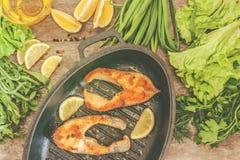 Испеченные рыбы форели стейка в чугуне формируют, вокруг зеленых цветов, листья, Стоковое Изображение