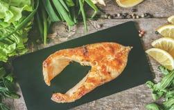 Испеченные рыбы форели стейка на каменной доске, вокруг зеленых цветов, листья, Стоковая Фотография