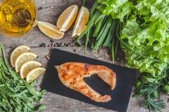 Испеченные рыбы форели стейка на каменной доске, вокруг зеленых цветов, листья, Стоковое Изображение