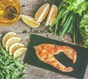 Испеченные рыбы форели стейка на каменной доске, вокруг зеленых цветов, листья, Стоковые Фотографии RF