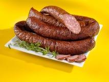 Испеченные сосиски на плите и желтой предпосылке Стоковые Изображения