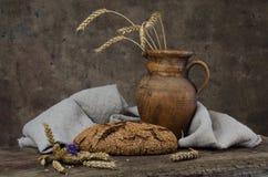 Испеченные хлеб, глиняный кувшин и колоски на деревянных досках Стоковая Фотография