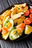 Испеченный авокадо заполненный с яичками и семгами, свежими томатами и f Стоковая Фотография RF