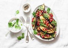 Испеченный баклажан с фета, греческим йогуртом, соусом cilantro и семенами гранатового дерева на светлой предпосылке, взгляде све стоковые изображения rf