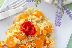 Испеченный красный пеец и сваренный белый рис с очень вкусными морковами на белых керамических плите и вилке и ноже столового при стоковая фотография rf