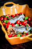 Испеченный морской волк с томатами и базилик на деревенском деревянном backgroun Стоковое фото RF