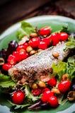Испеченный морской волк с томатами и базилик на деревенском деревянном backgroun Стоковые Изображения RF