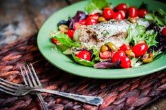 Испеченный морской волк с томатами и базилик на деревенском деревянном backgroun Стоковые Фотографии RF