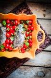 Испеченный морской волк с томатами и базилик на деревенском деревянном backgroun Стоковая Фотография RF