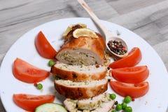 Испеченный цыпленок свертывает с томатом и лимоном и специями на белой плите на белом деревянном столе Стоковое Фото