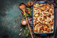 Испеченный цыпленок с овощами в сотейнике с деревянной ложкой и свежими травами и специями Стоковые Фотографии RF