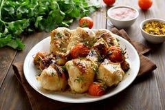 Испеченный drumstick цыпленка и зажаренные в духовке томаты Стоковое Фото