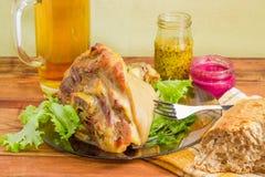 Испеченный hock ветчины на стеклянном блюде с condiments и пивом Стоковые Фото
