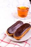 Испечет eclairs, и чашку чаю с циннамоном Стоковые Изображения RF