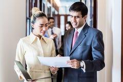 Исполнительная власть и секретарша стоя в прихожей офиса обсуждая бумаги Стоковое Изображение RF
