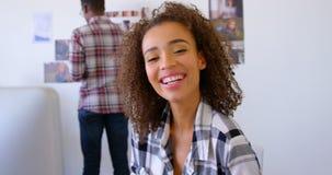 Исполнительная власть милой смешанн-гонки женская усмехаясь на столе в современном офисе 4k видеоматериал