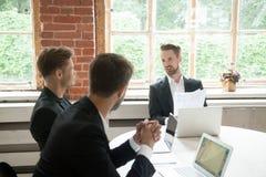 Исполнительная мужская команда обсуждая новый проект на встрече в boardro Стоковое фото RF