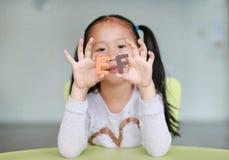 Исполнительные функции прелестного маленького азиатского алфавита удерживания девушки ребенка EF отправляют SMS на ее стороне o стоковое изображение rf