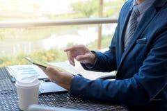 Исполнительный бизнесмен работая анализирующ вклад используя таблетку, стоковая фотография rf