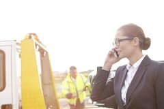 Исполнительный говорить на мобильном телефоне пока тележка отбуксировки водителя против неба стоковое изображение rf