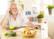 использование пенсионера мобильного телефона завтрака здоровое Стоковое фото RF