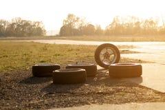 Используемые колеса смещения на следе автомобиля с заходом солнца стоковые изображения rf