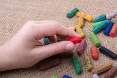 Используемые crayons цвета и рука подростков Стоковые Фотографии RF