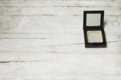 Используемый порошок компакта отжатый на белой деревянной предпосылке стоковые изображения